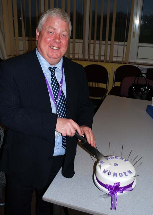 Academy at Worden Headteacher cutting the cake yo celebrate academy status